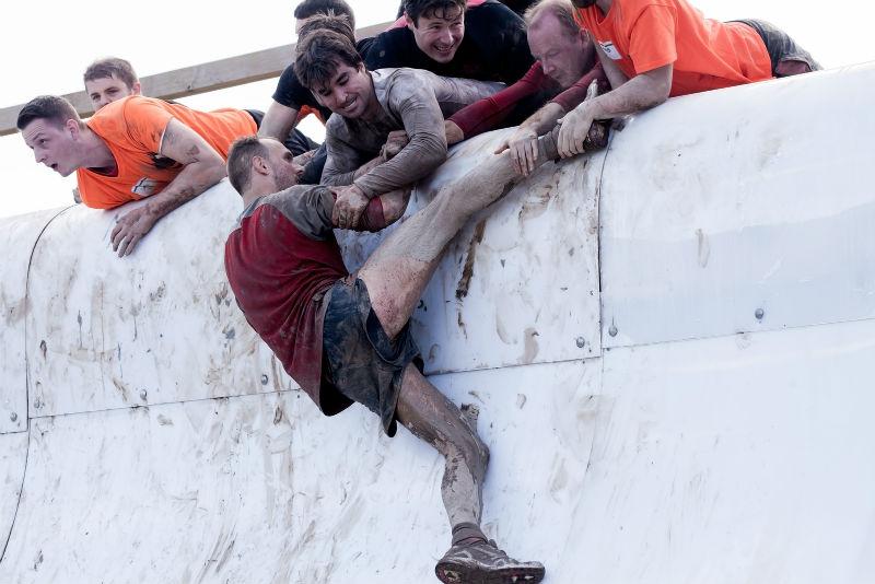 גברים עוזרים אחד לשני לעלות על קיר