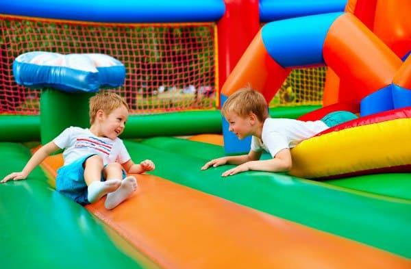 ילדים מחייכים שוכבים על מתקן מתנפח צבעוני