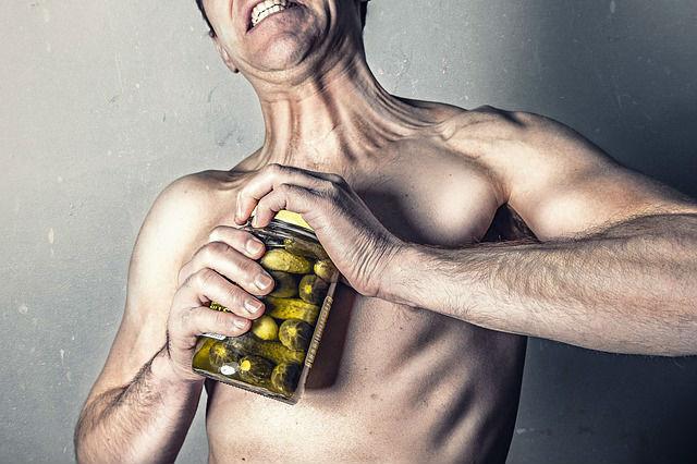 גבר מנסה לפתוח צנצנת חמוצים