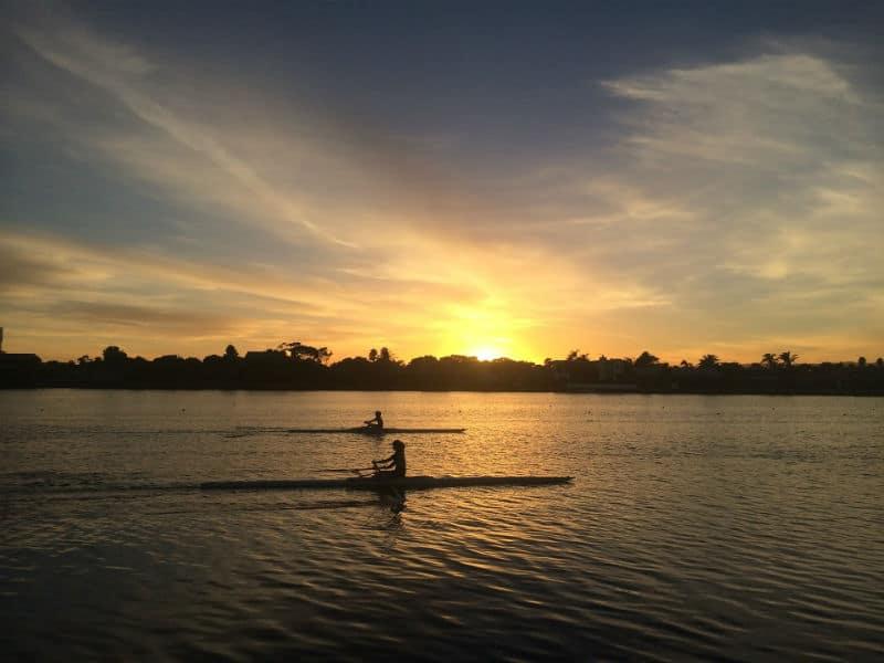 2 ספורטאים חותרים בנהר על רקע שקיעה