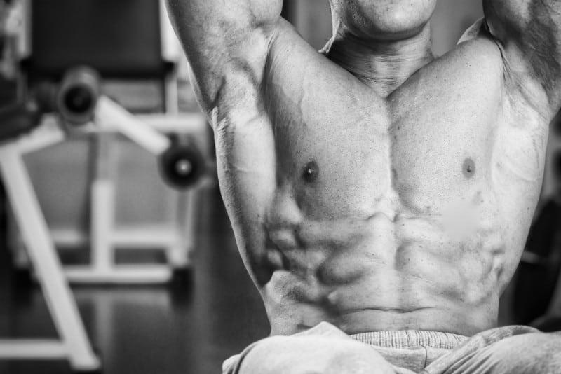 פוקוס על שרירי הבטן של גבר שמבצע תרגילים לחיזוקם