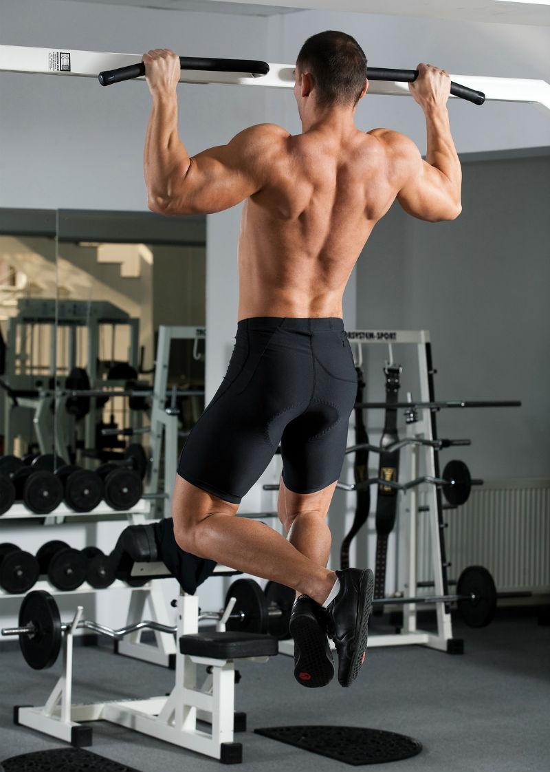 גבר שרירי עם גב חשוף על מתקן מתח מקבילים בזמן תרגילי מתח