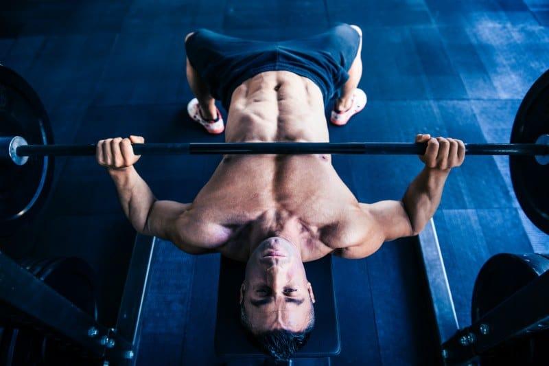 גבר שרירי מבצע תרגילי הרמת משקולת לחיזוק שרירי החזה
