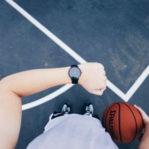 גבר מחזיק כדור ומביט על השעון